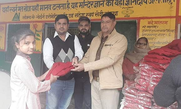 बच्चो को गर्म कपडे वितरित करते हुए पार्षद अरविन्द चौधरी व चौकी इंचार्ज नरपाल सिंह