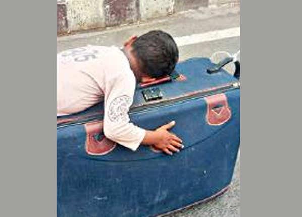 सूटकेस पर ही सो गया बच्चा